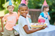 Boy holding cake at birthday party