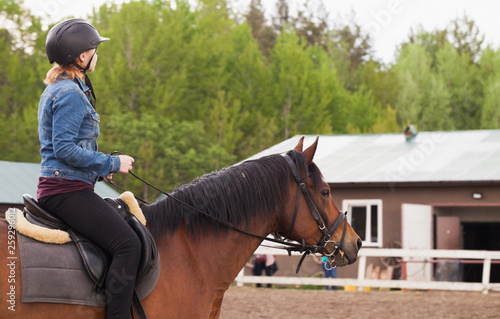 Teenage girl rides brown horse - 259296012