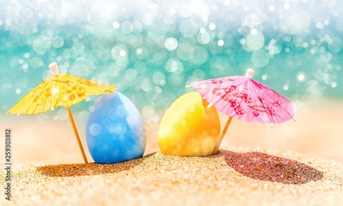 Leinwandbild Motiv Colorful easter eggs on ocean beach