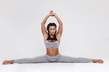 Young amazing strong sports fitness woman posing isolated over white wall background make exercises.