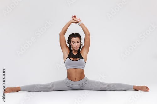 Fototapeten Fitness Young amazing strong sports fitness woman posing isolated over white wall background make exercises.