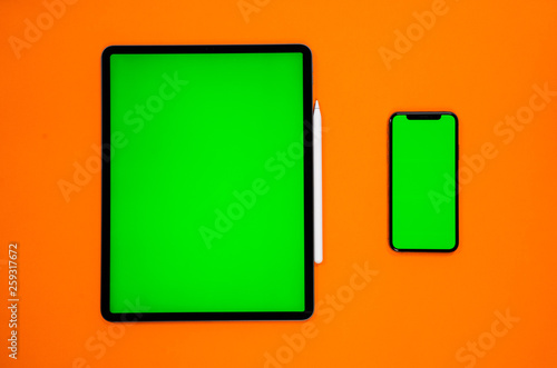new tablet on a Orange background with a keyboard and pen, and green screen top view - 259317672