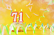 Seventy one years birthday. Cupcake with burning candles in the form of number 71. Bright yellow background with copy space