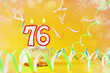 Seventy six years birthday. Cupcake with burning candles in the form of number 76. Bright yellow background with copy space