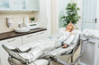 Quadro Blonde girl lying on beauty couch during pressotherapy session in clinic