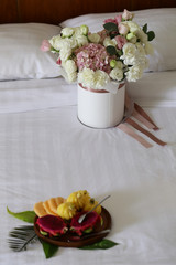 flowers and fruit in bed, hotel room