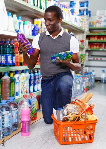 Mature afro man buying washing chemicals in supermarket © JackF