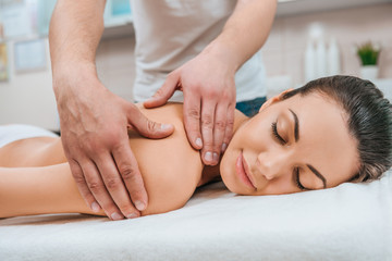 Partial view of masseur doing back massage to relaxed girl on massage table