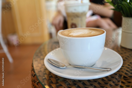 white cup of hot coffee drink put on table in cafe restaurant