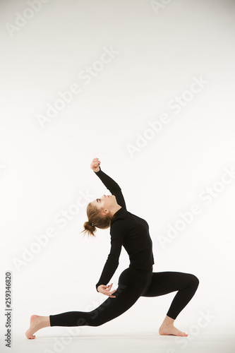 A girl in black clothes on a white isolated background performs dance and ballet poses and movements. © Fotoproff