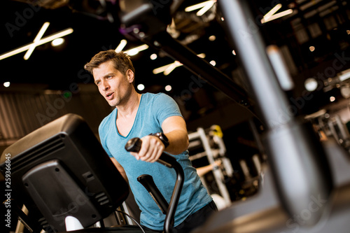 canvas print picture Man doing exercise on elliptical cross trainer in sport fitness gym club