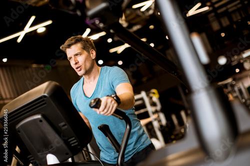 Leinwanddruck Bild Man doing exercise on elliptical cross trainer in sport fitness gym club