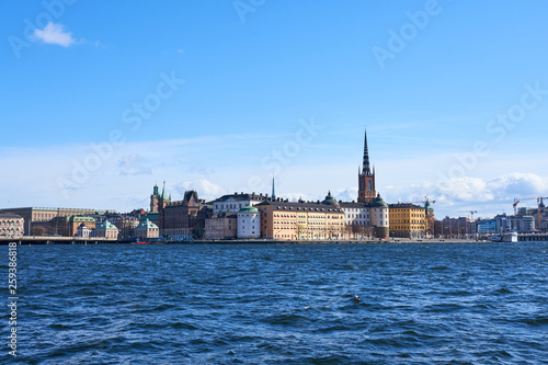 Old city of Stockholm with waves on blue water under the blue cloudy sky in sunshine.