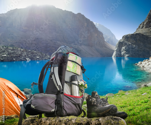 Hiking equipment and camping tent in mountains