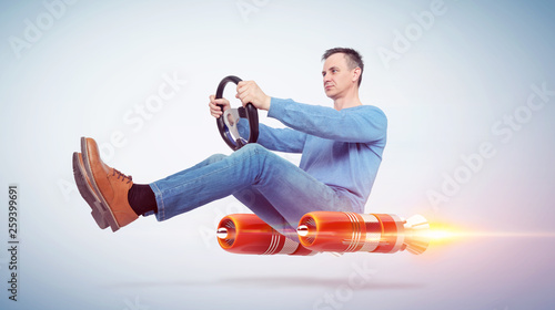 Man in casual wear car driver with a wheel, concept of rocket alternative transport