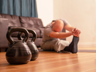 Fitness concept, kettlebell in focus, bold man doing strech excercise on a floor out of focus, workout at home.