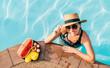 Leinwanddruck Bild - Smiling woman in straw hat in sunglasses swimming in pool and enjoying fresh tropical fruits