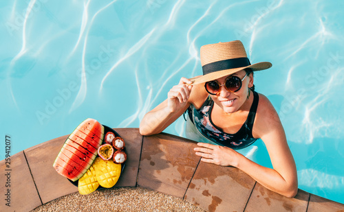 Leinwanddruck Bild Smiling woman in straw hat in sunglasses swimming in pool and enjoying fresh tropical fruits
