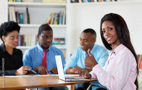 Successful african american businesswoman with team and computer