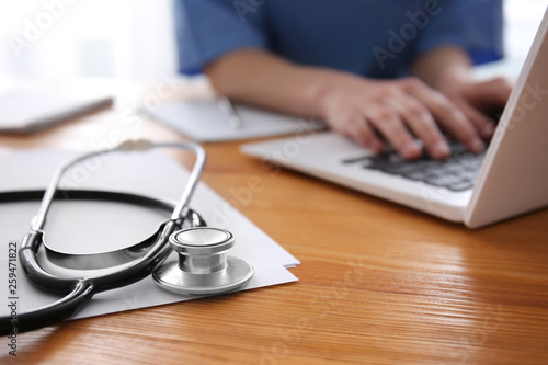 Leinwanddruck Bild Stethoscope and doctor working at table