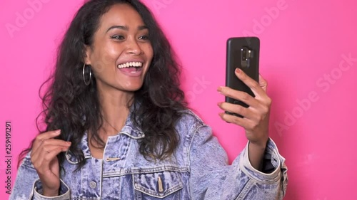 close up footage of pretty asian woman video calling on her mobilephone with pink background