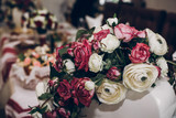 stylish roses in vases on table at wedding reception, decor at celebration