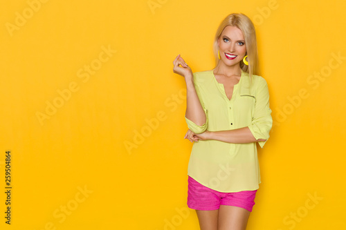 canvas print picture Smiling Beautiful Blond Woman In Yellow Shirt And Pink Shorts