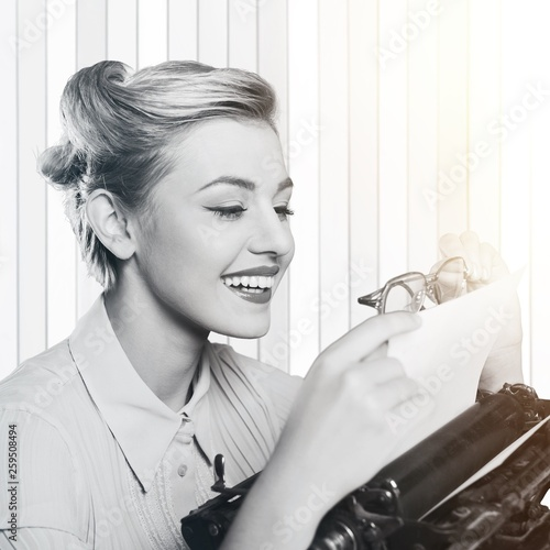 fototapeta na ścianę Attractive young woman working on vintage typewriter on background