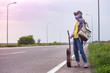 Leinwandbild Motiv  girl with a guitar hitch-hiking