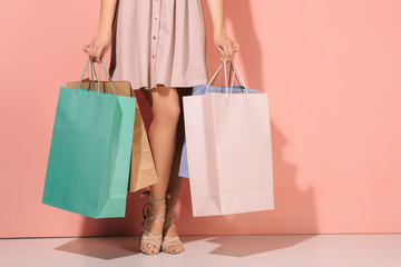 cropped view of woman holding shopping bags on pink background