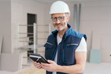 Builder holding a tablet and journal