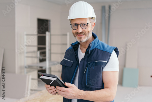 Builder holding a tablet and journal - 259546858