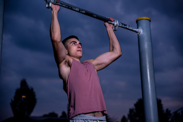 Young male athlete doing warm up and training in park during sunset.