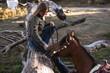 canvas print picture - Frau sitzt auf Baumstamm und lacht das Pferd an