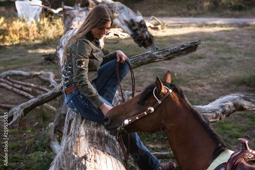 canvas print picture Frau sitzt auf Baumstamm und lacht das Pferd an