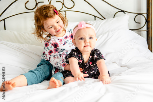 The Two sister baby in white bed at home