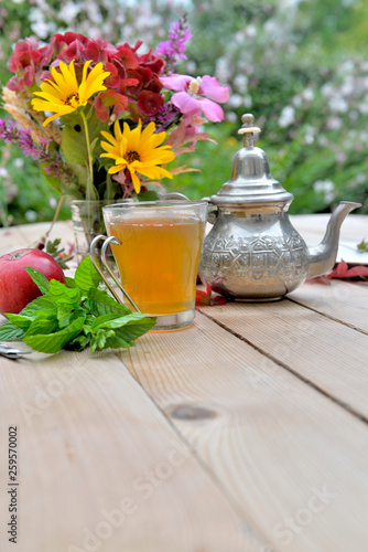 cup of mint tea with colorful bouquet of flowers on a table in garden © coco