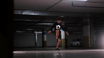 Underground parking lot. A soccer man training his football skills. Balance the ball on his knee