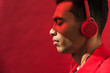 side view of handsome mixed race man in headphones with eyes closed isolated on red with copy space