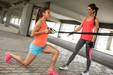 Two young female work out on trx,suspension trainer.Outdoor workout.
