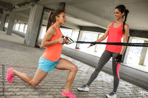 Fototapeten Fitness Two young female work out on trx,suspension trainer.Outdoor workout.