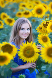 Young beautiful girl in a field of sunflowers