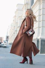 Stylish fashionable blonde woman wearing coat and sunglasses, street style photo