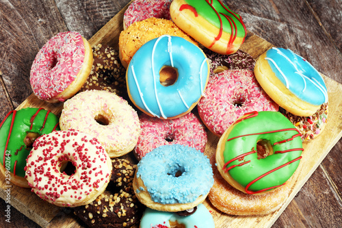 assorted donuts with chocolate frosted, pink glazed and sprinkles donuts. © beats_