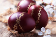 Quadro Dark red Easter eggs with gold pattern, apricot flowers,  rustic wooden background, selective focus