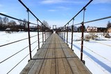 suspension bridge over snow-covered river
