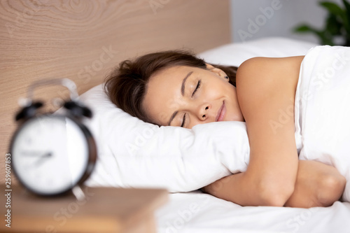 Pretty female sleeping on bed alarm clock on bedside table - 259607853
