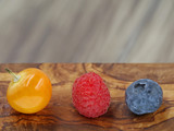 close up of raspberry, blueberry and berry of physalis on wooden background with copy space