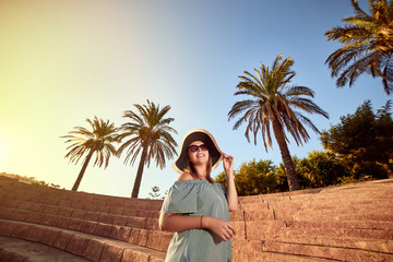 Young beautiful woman in beach hat walking on the steps of an ancient amphitheater at sunny day in Bodrum, Turkey. Vacation Outdoors Seascape Summer Travel Concept