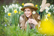 Leinwandbild Motiv Portrait a beautiful woman in straw hat with  daffodils flowers in the garden. Gardening.